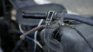 Close tracking shot across the handlebars of an old motorcycle.