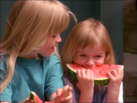 close up 2 blonde girls smiling + eating watermelon
