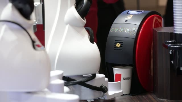 Close up a Kawasaki Heavy Industries Ltd twoarmed duAro robot places a cup into a Nestle SA Nescafe Gold Blend Barista 50 coffee machine during a...