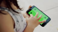 Close Up : A Little Girl Using smart phone with Green Screen