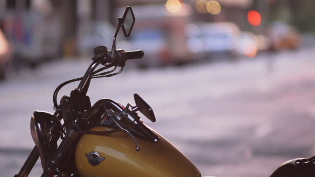 A close up a vintage motorcycle sits by the curb in New York