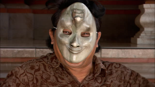 Close up actor wearing smiling mask and acting coy / Ubud, Bali, Indonesia