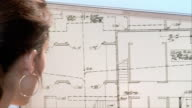 Close up architect looking at blueprint on computer