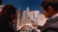 Close up architectural model / zoom out to businessman and woman holding model and looking out from roof at buildings / New York City