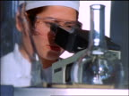 close up Asian female scientist in safety goggles looks into microscope / beakers in foreground