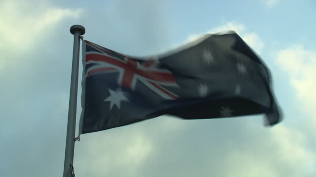 close up Australian flag fluttering flying in wind clouds move behind