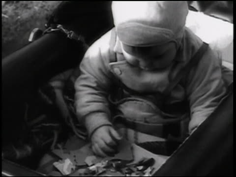 B/W 1938 close up baby in carriage playing with jigsaw puzzle / newsreel
