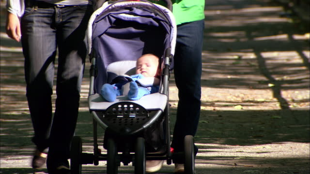 Close up baby in stroller / tilt up woman and man walking and pushing stroller