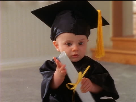 close up baby wearing cap + gown + putting diploma in his mouth