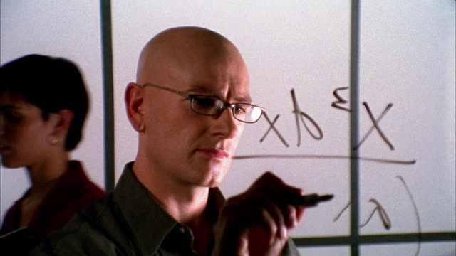 Close up bald man writing algebraic equation on transparent surface in front of him / 2 people pass in background