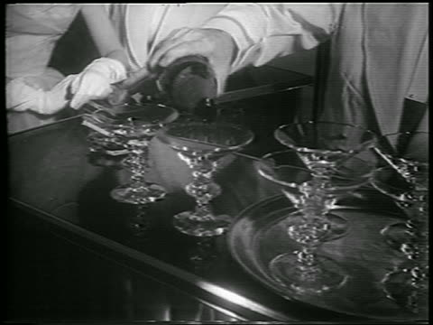 B/W 1953 close up bartender's hand pouring champagne into glasses on bar / newsreel