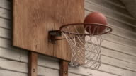 Close up basketballs bouncing off rim of hoop / basketballs going in basket