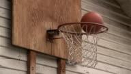 Close up basketballs bouncing off rim of hoop / basketballs going in basket