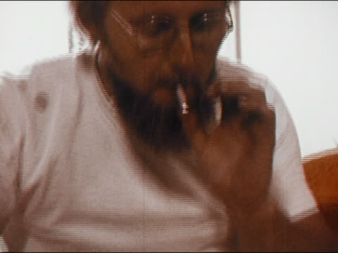 1971 close up bearded man lighting joint and smoking it / passing it to young man on his right