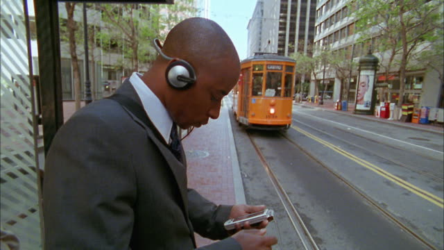 Close up Black businessman waiting for trolley / checking PDA / medium shot commuters waiting to board trolley
