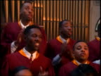 close up PAN Black gospel choir in robes singing + clapping in church