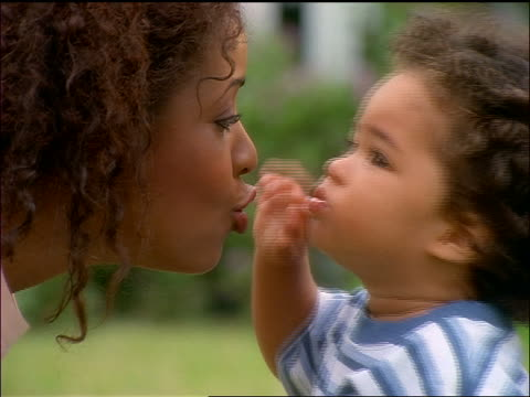 close up Black mother + baby kissing outdoors + pointing towards sky