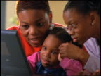 close up Black woman + two young girls working with laptop computer + talking indoors