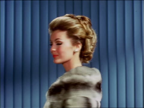 1968 close up blonde woman modeling chinchilla fur stole turning to camera indoors / industrial