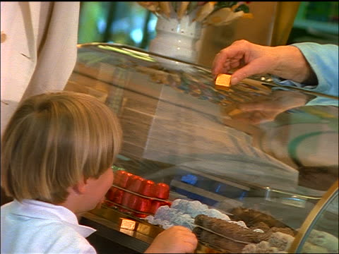 close up blonde woman + son at counter of candy store / hand of shopkeeper handing boy chocolate