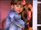 close up boy sitting in window hugging bloodhound dog