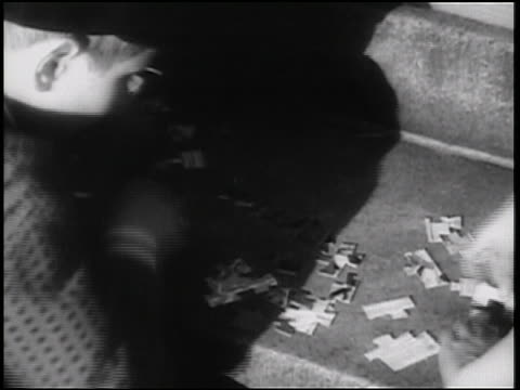 B/W 1938 close up boy sitting on steps outside playing with jigsaw puzzle / newsreel