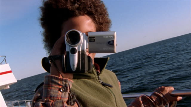 Close up boy standing on boat pointing video camera at CAM