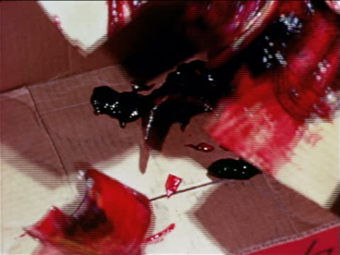 1965 close up broken glass jar of jam being poured onto piece of cardboard / educational