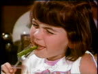 1969 close up brunette girl eating asparagus spear + making face / industrial