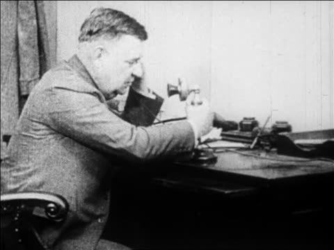 B/W 1929 close up businessman at desk in office talking on telephone / newsreel