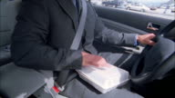 Close up businessman eating lunch while driving