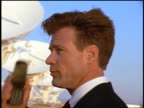 close up businessman talking on cellular phone in front of VLA radio telescope dishes / New Mexico