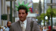 Close up businessman walking and wearing foam Statue of Liberty crown