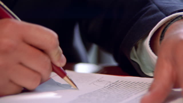 close up PAN businessman's hands singing document / contract
