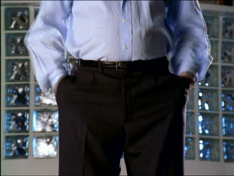 close up businessman's hands turning empty pants pockets inside out  / glass bricks in background