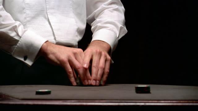 Close up casino worker shuffling deck of cards / dealing poker hands