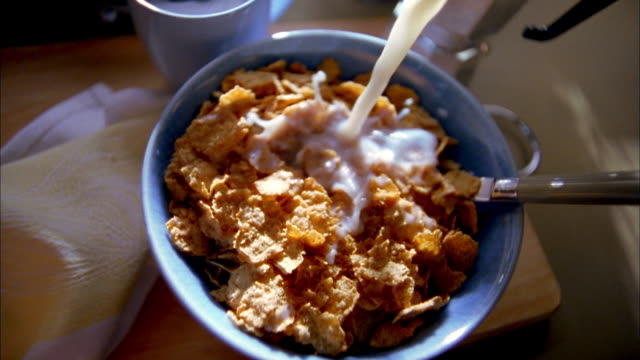 Close up cereal in blue bowl w/spoon and coffee cup next to it / milk pouring into bowl