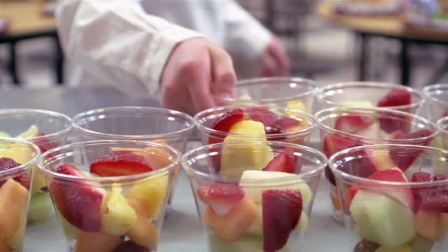 Close up children pick up fruit cups in school lunch line/ Goram, Maine