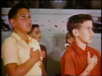 1953 close up children with hands on chests saying Pledge of Allegiance / educational