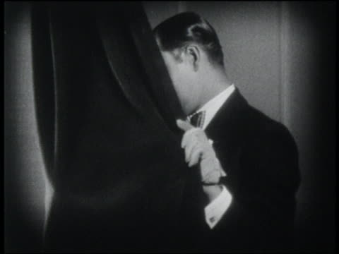 B/W 1920 close up couple pulls curtain away after just having kissed