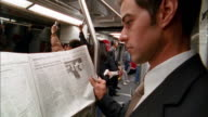 Close up crane shot commuter reading newspaper on subway