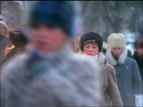 close up crowd of women in fur hats + winter coats walking towards camera in Winter / Moscow, Russia