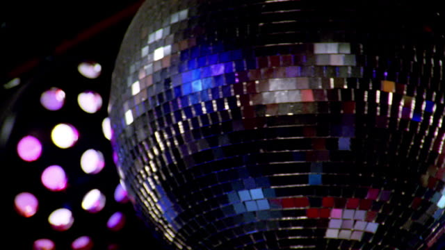 Close up disco ball spinning with lights flashing