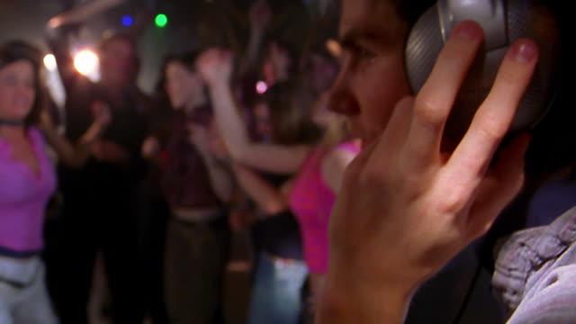 Close up dj with headphones / wide shot crane shot to medium shot people dancing