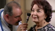 Close up doctor examining senior woman's ears with scope / El Paso, Texas
