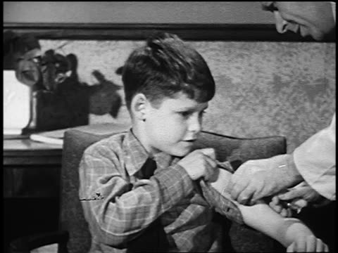 B/W 1950 close up doctor giving shot in boy's arm with hypodermic needle