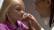 Close up doctor letting young girl speak into stethoscope and listen to her own heartbeat