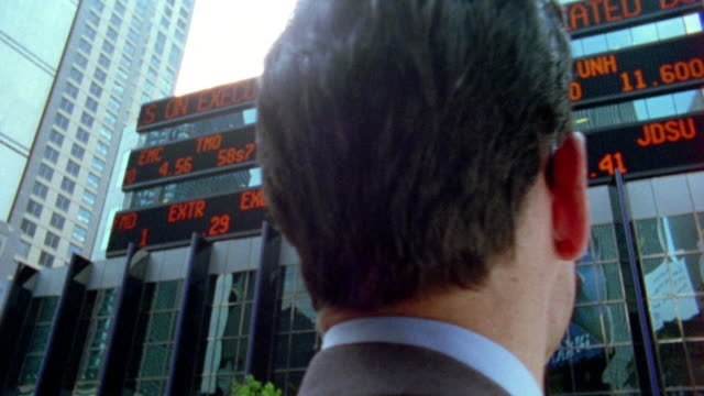 Close up dolly shot businessman looking at digital stock ticker board outdoors / NYC