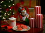 close up dolly shot cookies on dish + mug of hot cocoa on table with candles + Santa Claus statue /Christmas tree background