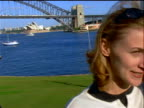 close up dolly shot past woman talking on cellular phone with bridge + Opera House in background / Sydney, Australia